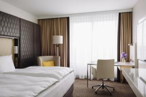 A bed or beds in a room at Pullman Berlin Schweizerhof