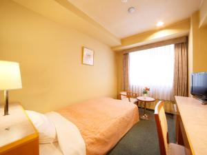 A bed or beds in a room at Hotel Pearl City Sendai