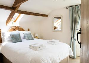 A bed or beds in a room at The Neuadd Cottages