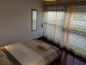Uma cama ou camas num quarto em São Brás Apartment