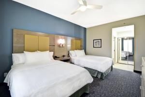 A bed or beds in a room at Homewood Suites by Hilton Orlando Theme Parks