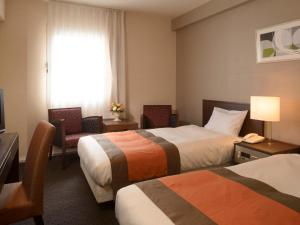 A bed or beds in a room at Hotel Crown Palais Aomori