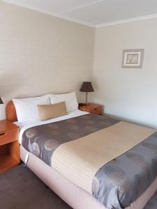 A bed or beds in a room at Hacienda Motel Geelong