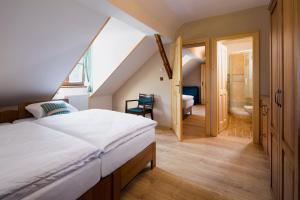 A bed or beds in a room at Wellness Hotel Florián České Žleby