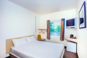 A bed or beds in a room at ibis Budget Coffs Harbour