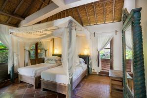 Ein Bett oder Betten in einem Zimmer der Unterkunft Puri Ganesha Homes by the BEACH