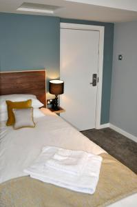 A bed or beds in a room at The Coach Hotel