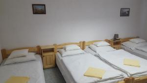 A bed or beds in a room at OKSZI Vendégház