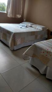 A bed or beds in a room at Pousada Santana