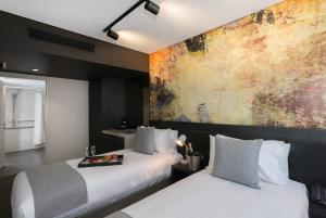 A bed or beds in a room at Mantra Richmont Hotel