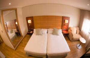 A bed or beds in a room at Sercotel Gran Fama
