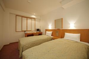 A bed or beds in a room at Smile Hotel Nara