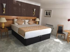 A bed or beds in a room at Harefield Manor Hotel