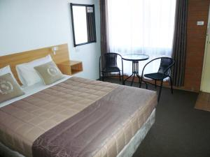 A bed or beds in a room at Grong Grong Motor Inn