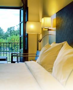 A bed or beds in a room at Oca Vila de Allariz Hotel & Spa