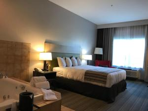 A bed or beds in a room at Country Inn & Suites by Radisson, Fond du Lac, WI