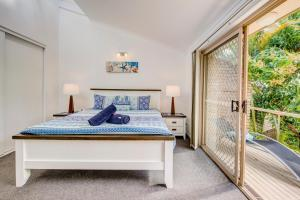 A bed or beds in a room at Palm Haven - Beachy Byron Townhouse
