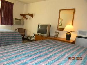 A bed or beds in a room at American Inn-Alexander City