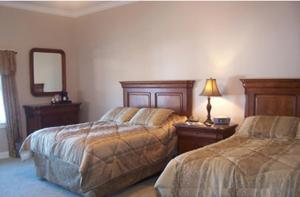 A bed or beds in a room at Townsend Manor Inn