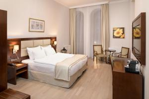 A bed or beds in a room at Concorde Old Bucharest Hotel