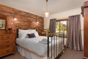 A bed or beds in a room at Killynaught Spa Cottages