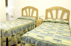 A bed or beds in a room at Hostal Las Torres