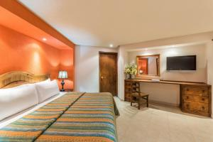A bed or beds in a room at Hotel Abadia Tradicional