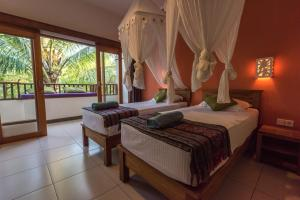 A bed or beds in a room at Arjuna Homestay