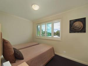 A bed or beds in a room at Pacific Blue Townhouse 358, 265 Sandy Point Road