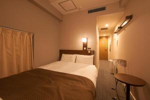 A bed or beds in a room at Dormy Inn Shinsaibashi Hot Spring