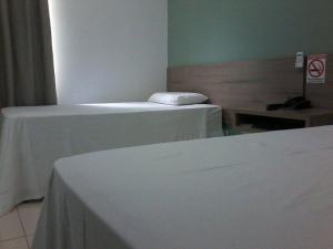 A bed or beds in a room at Hotel e Locadora Vizon