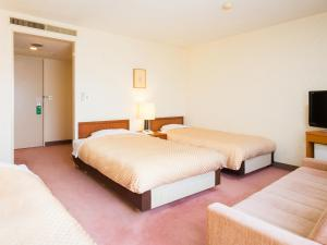 A bed or beds in a room at Yatsushiro Grand Hotel