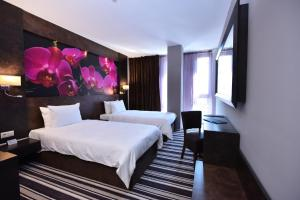 A bed or beds in a room at Best Boutique Hotel
