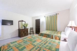 A bed or beds in a room at Hotel Abadia Plaza