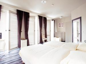 A bed or beds in a room at Thermae Grimbergen Hotel