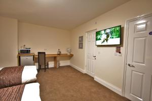 A television and/or entertainment center at New County Hotel by RoomsBooked
