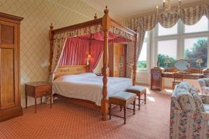 A bed or beds in a room at Tillmouth Park Country House Hotel