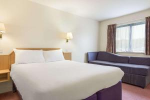 A bed or beds in a room at Days Inn Chesterfield - Tibshelf