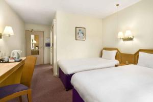 A bed or beds in a room at Days Inn Durham