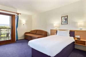 A bed or beds in a room at Days Inn Lockerbie - Annandale Water