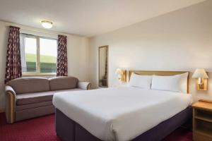 A bed or beds in a room at Days Inn Tewkesbury