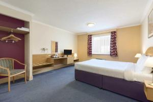 A bed or beds in a room at Days Inn Watford Gap