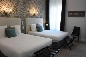 A bed or beds in a room at Régina Boutique Hotel
