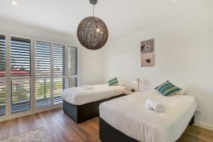 A bed or beds in a room at Magnificent Beach House