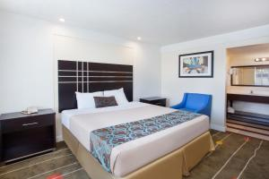 A bed or beds in a room at Travelodge by Wyndham Fresno Yosemite Area