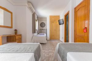A bed or beds in a room at Hostal Dinamarca