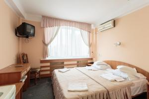 A bed or beds in a room at Druzhba Service Hotel