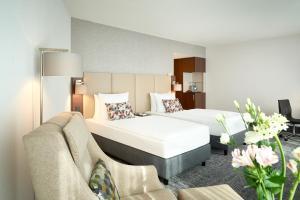 A bed or beds in a room at Dorint An den Westfalenhallen Dortmund