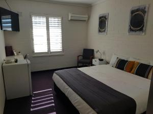 A bed or beds in a room at Morphett Arms Hotel