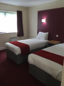 A bed or beds in a room at Days Inn Maidstone